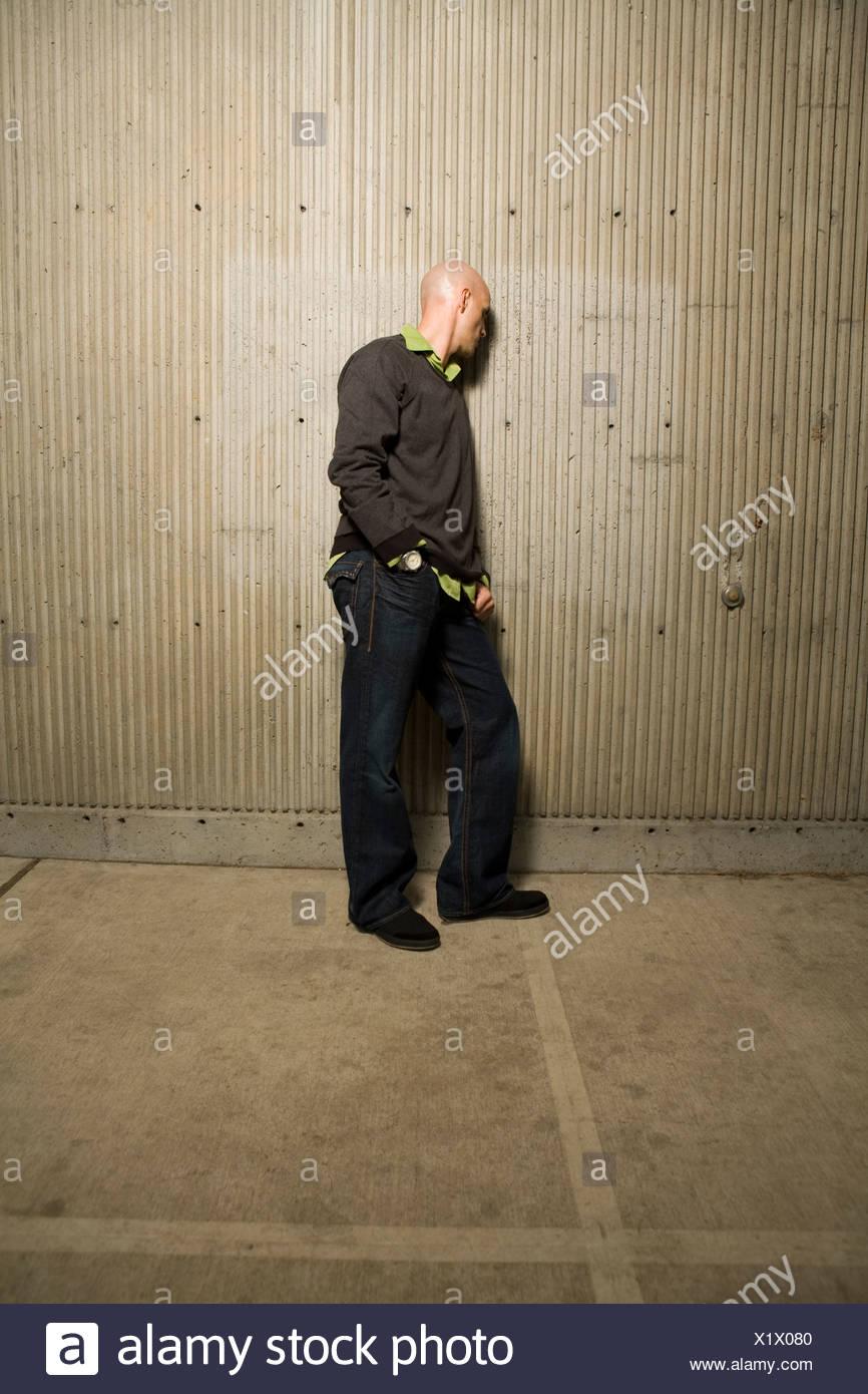 Imagen de longitud completa del hombre orientado hacia un muro de cemento Imagen De Stock