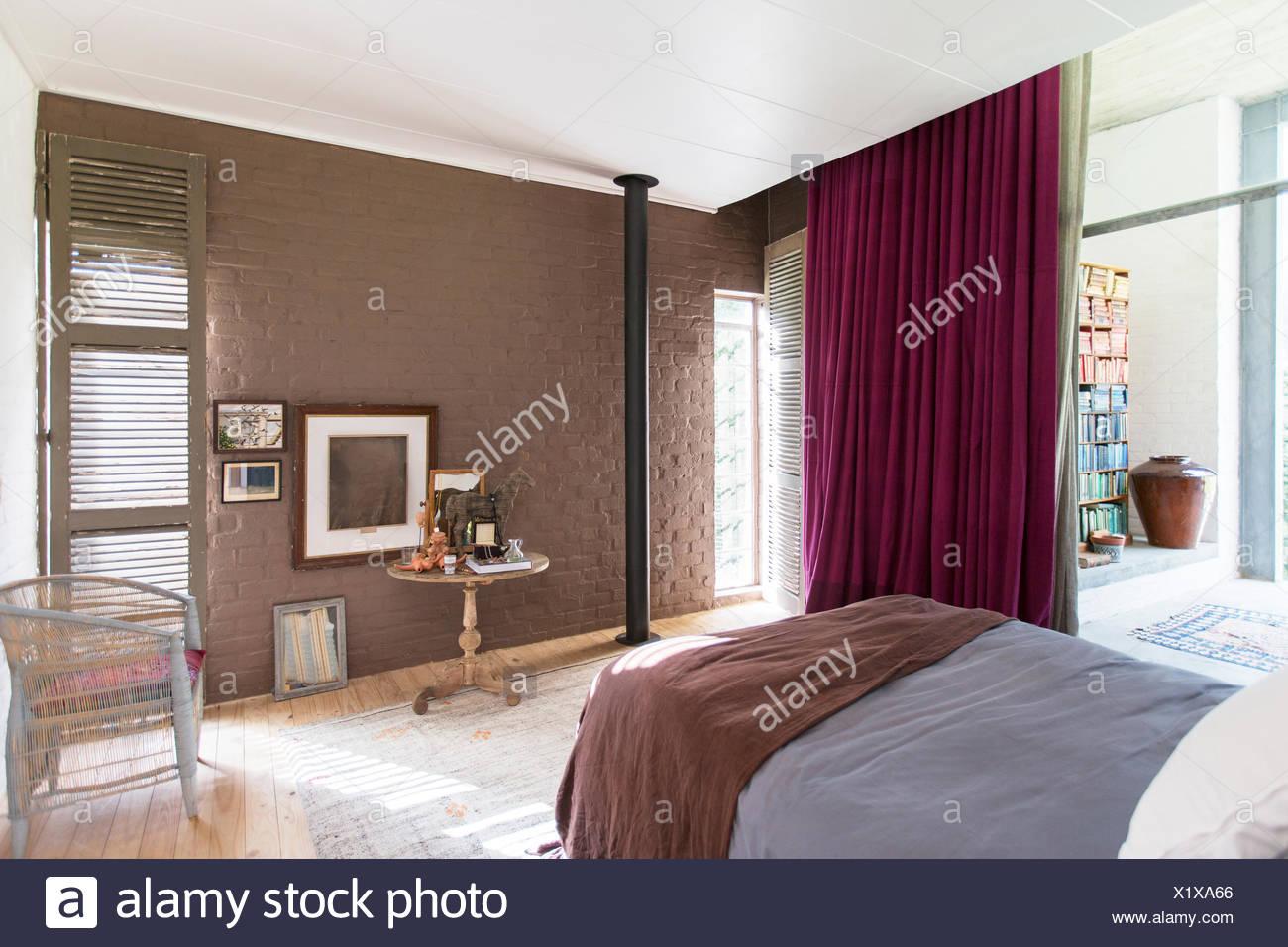 Cama, Mesa lateral y fotografías en dormitorio rústico Imagen De Stock