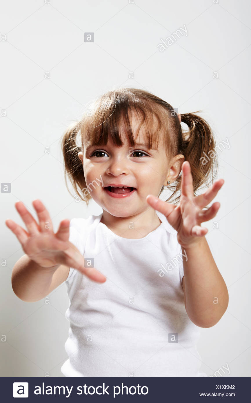 Retrato de joven con pigtails, con manos arriba Foto de stock