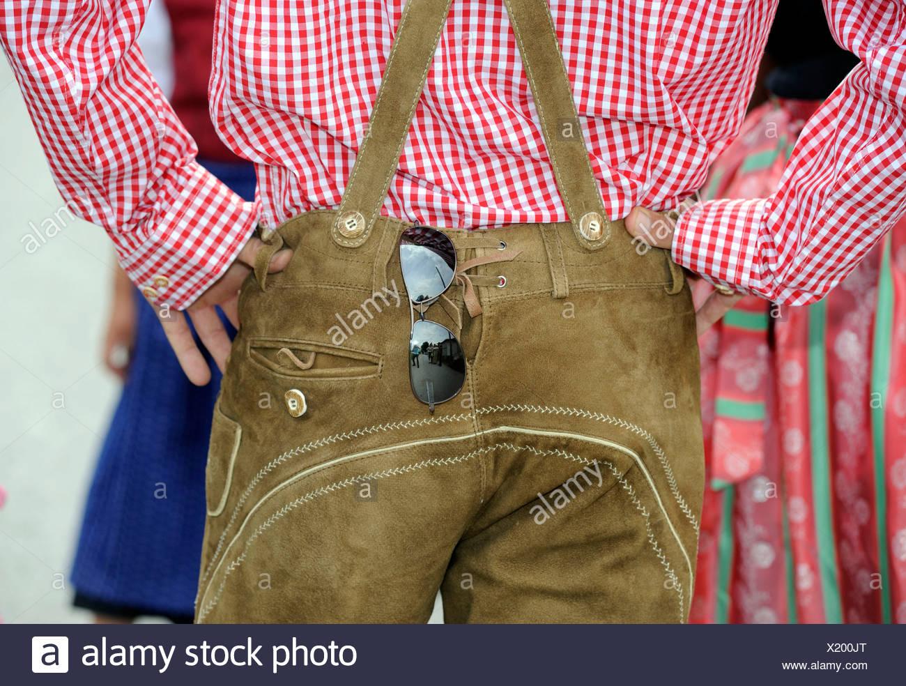 fa0a9f0fdf Pantalones de cuero y camisa a cuadros, trajes tradicionales, con gafas de  sol Imagen