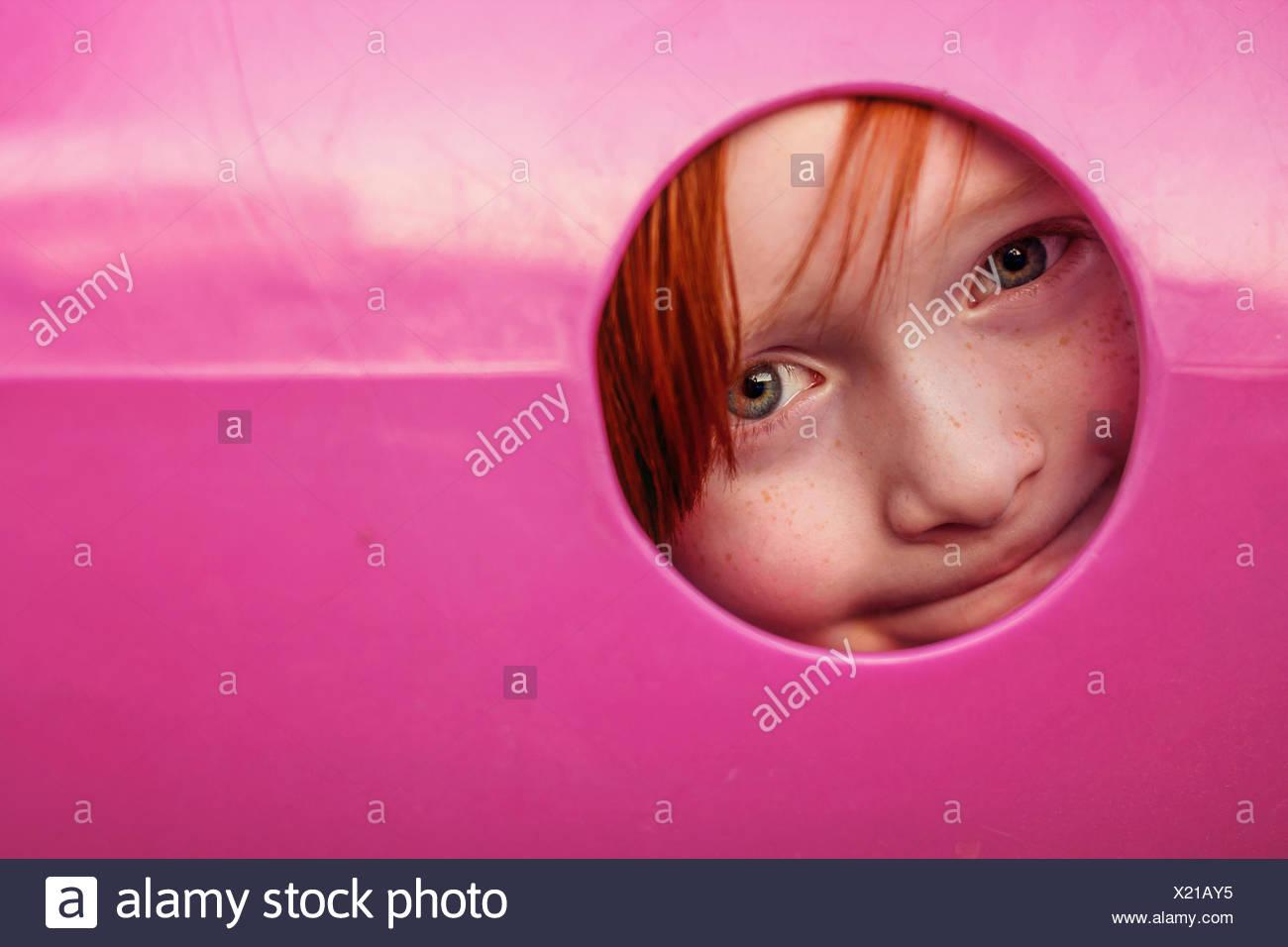 Joven peeking a través del agujero en el túnel de recreo Foto de stock