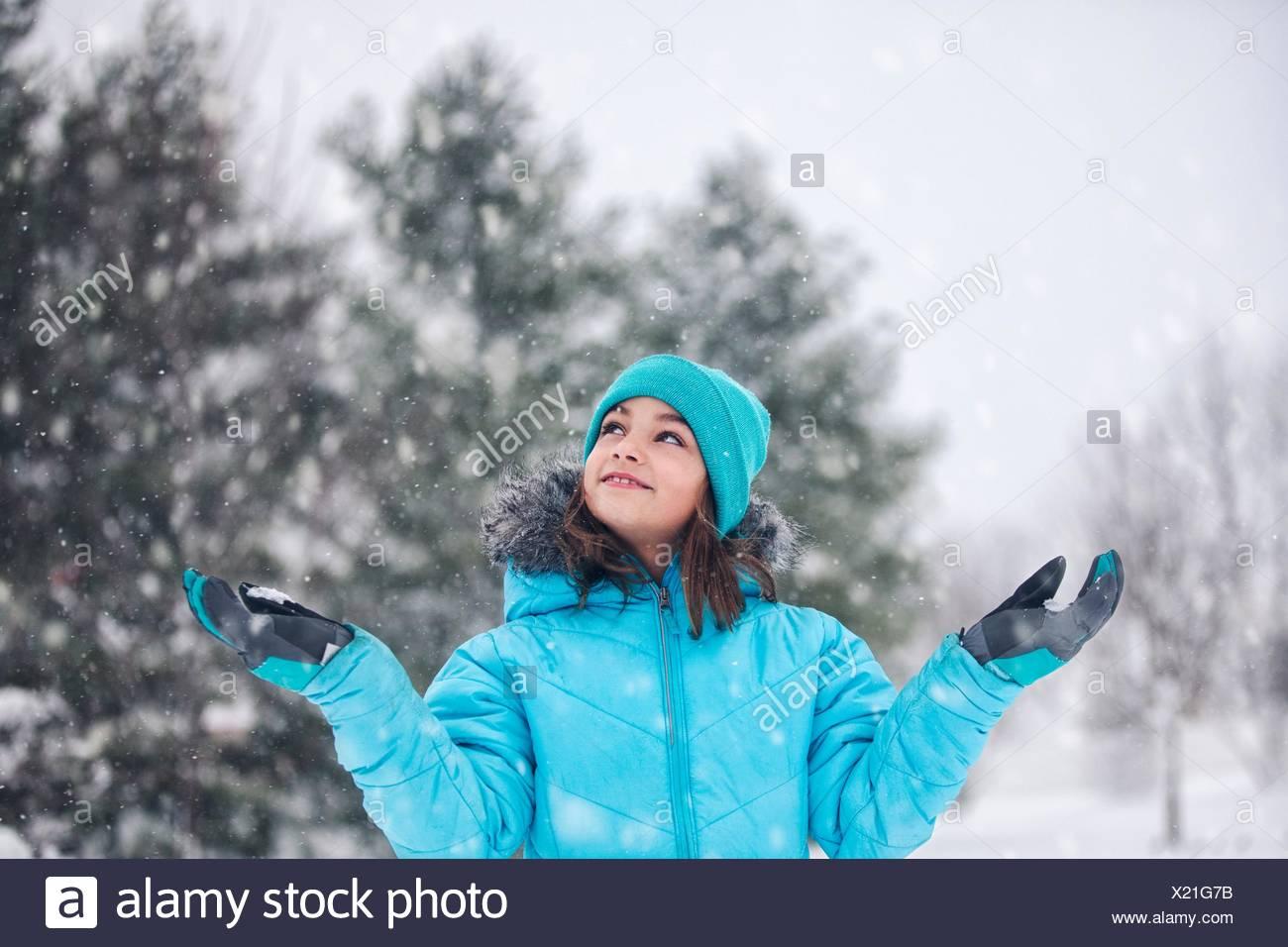 Vestida de turquesa tejer sombrero y abrigo, brazos levantados, manos atrapando nieve, mirando sonriente Foto de stock
