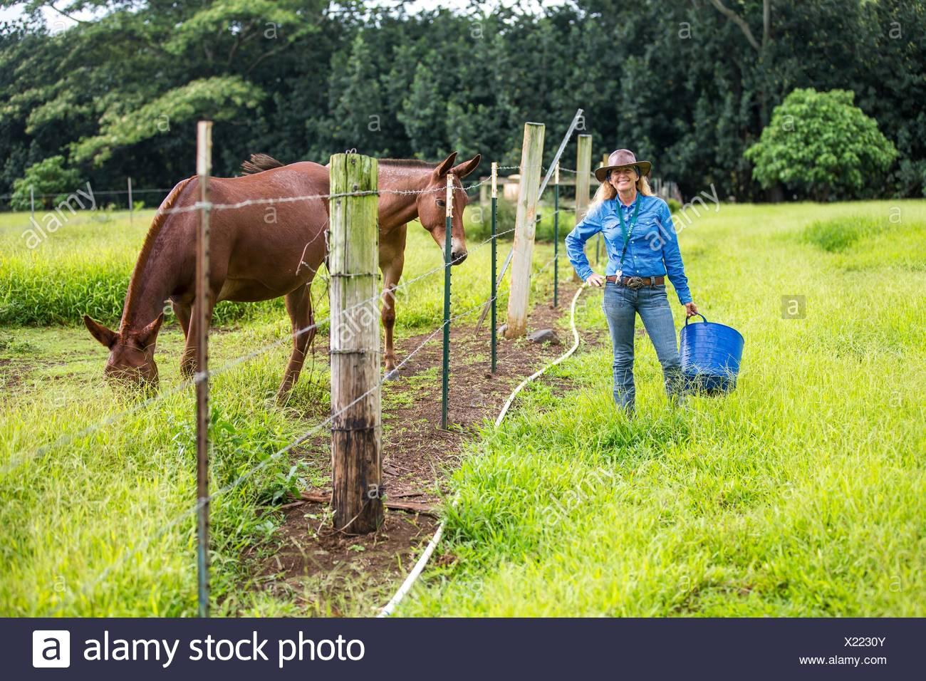 Retrato de mujer madura, en campo, de pie junto a caballo Foto de stock