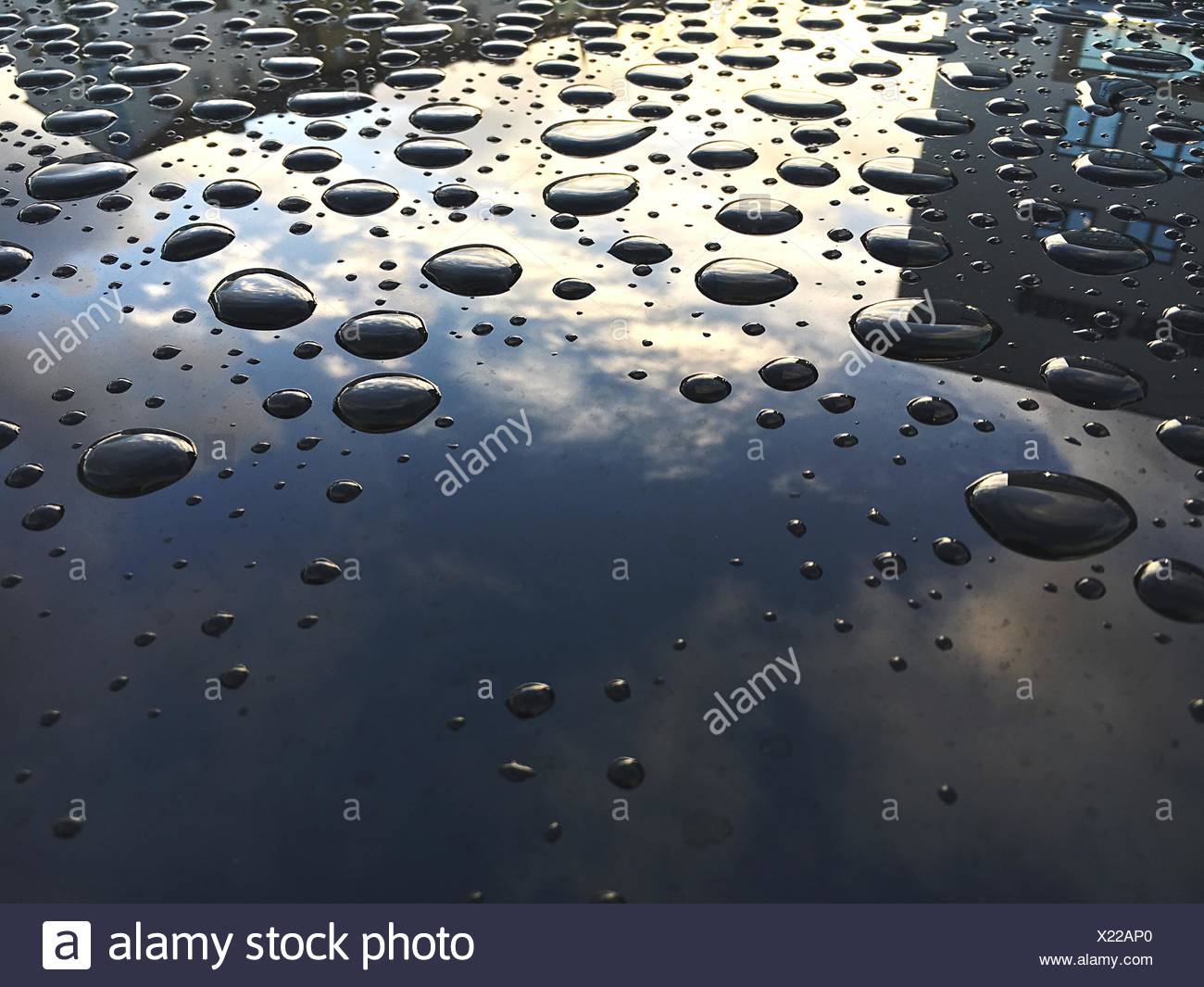 Primer plano de agua cae sobre el capó de coche Imagen De Stock