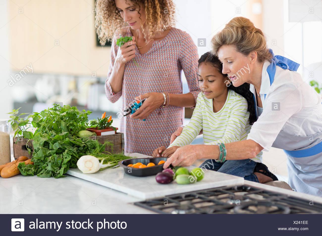 Mujer mayor con su hija y su nieta en la cocina Imagen De Stock