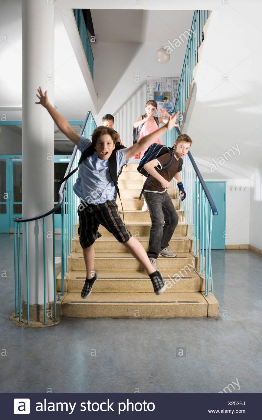 Cuatro pre-adolescentes niños corriendo escaleras abajo emocionado Imagen De Stock