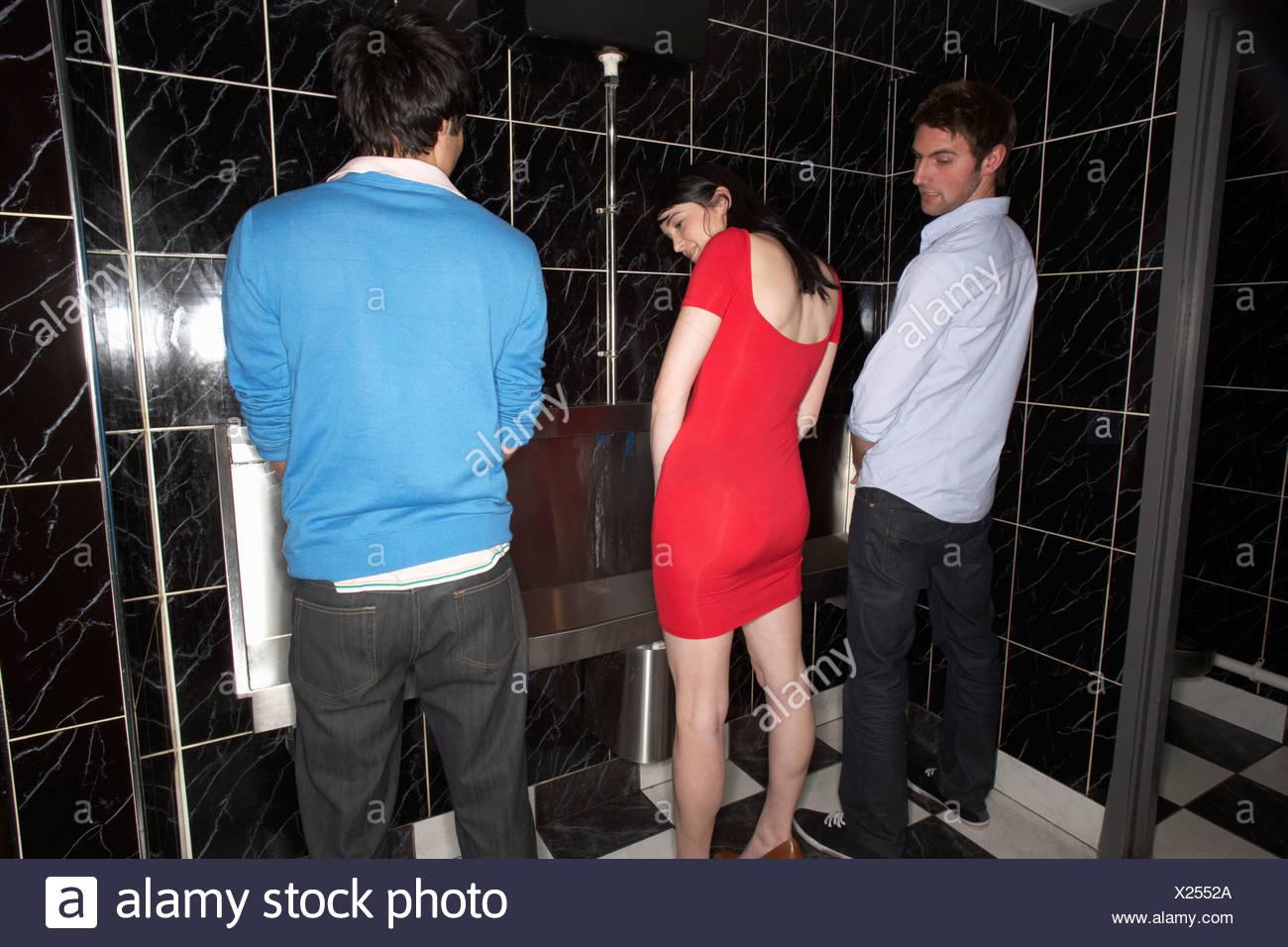 Una mujer y dos hombres de pie en mens urinal Imagen De Stock