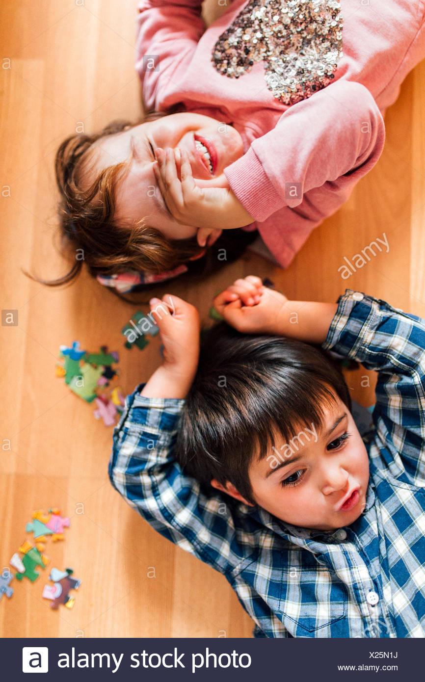 Chico y chica tumbados en el suelo Imagen De Stock