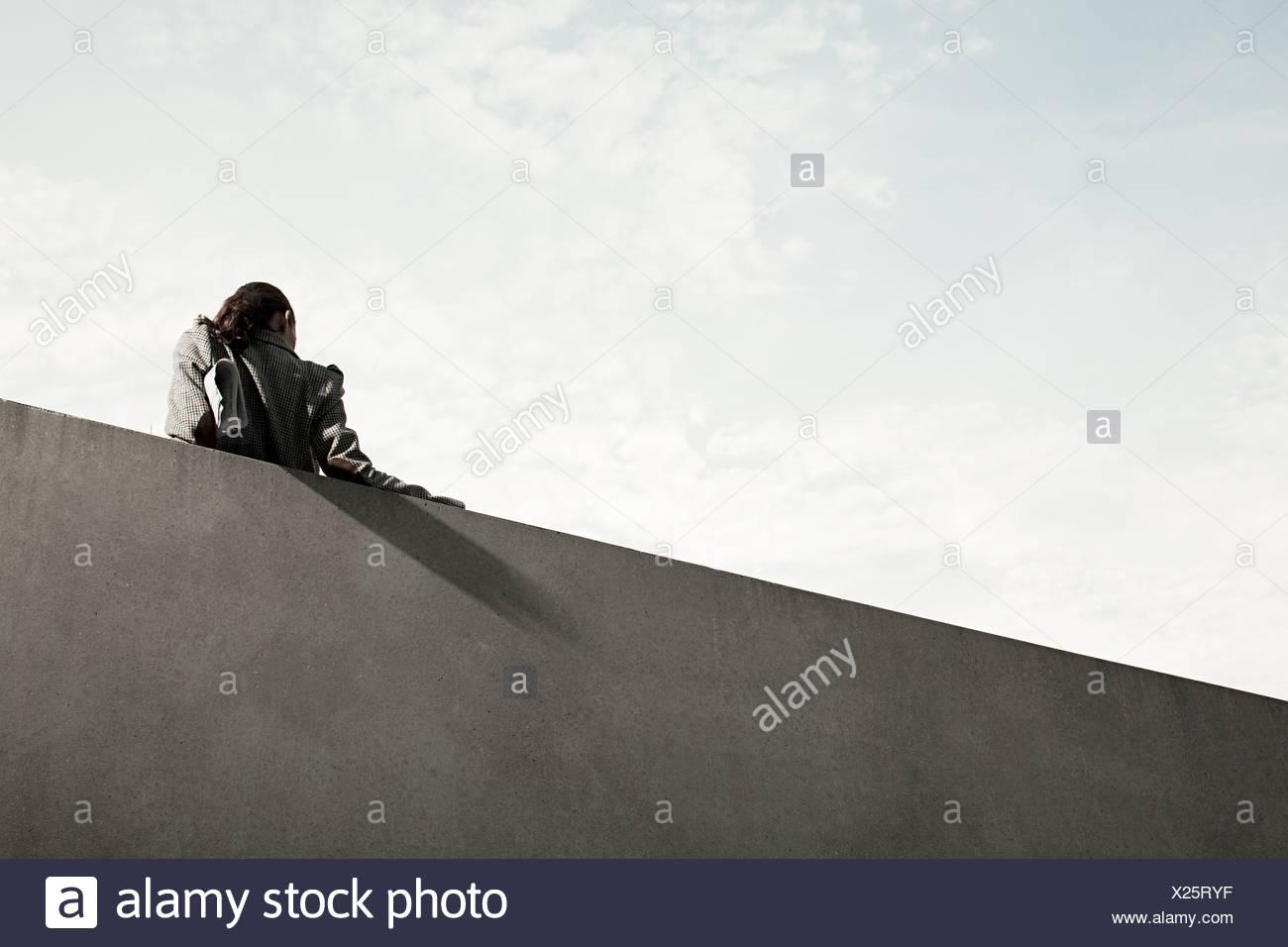 La empresaria por pared, vista trasera, bajo el ángulo Imagen De Stock