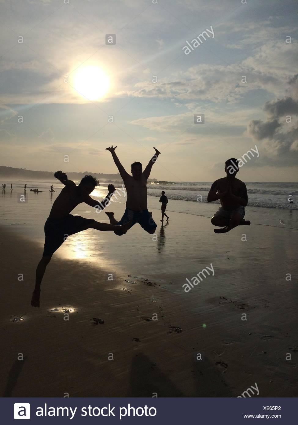 Longitud total en silueta amigos saltando en la playa contra el cielo Imagen De Stock
