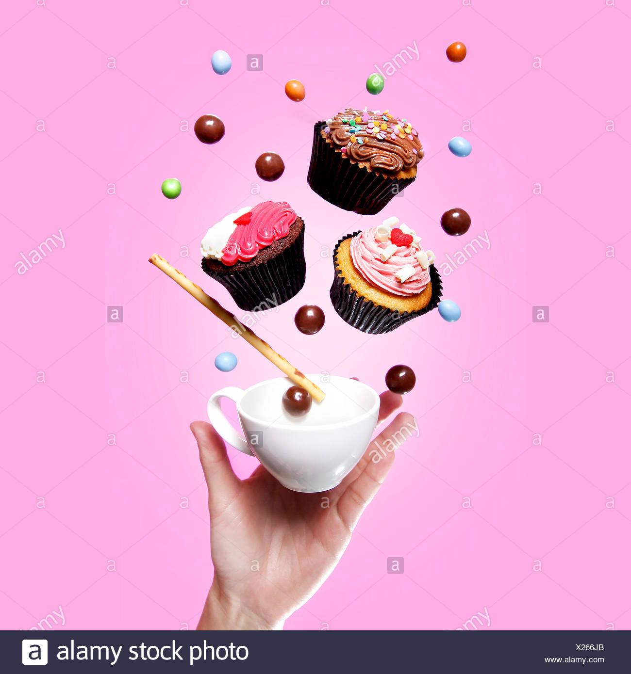 Flying pastelitos, tetera, dulces y una mano Imagen De Stock