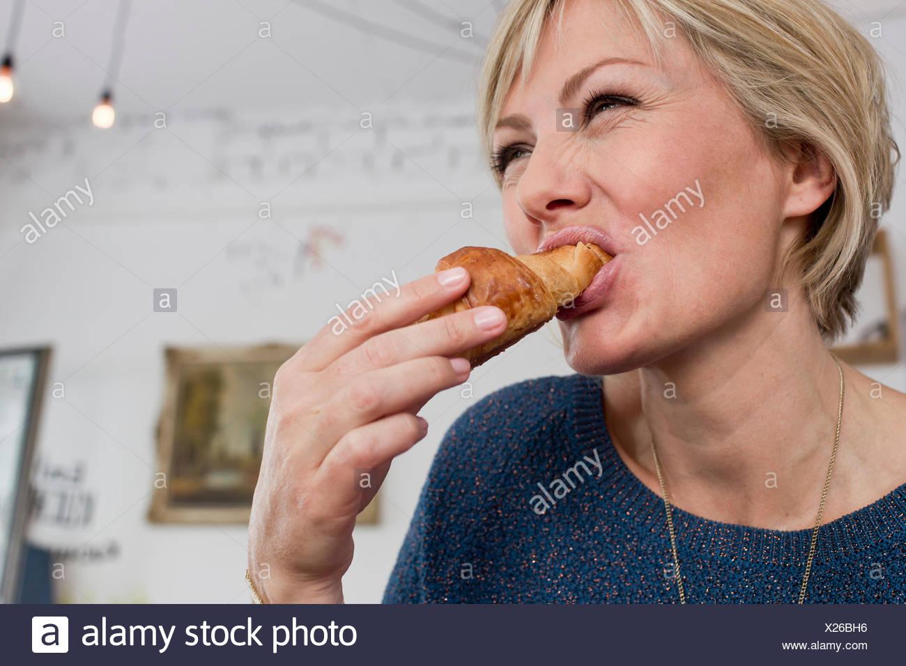 Mujer adulta media comiendo croissant Foto de stock