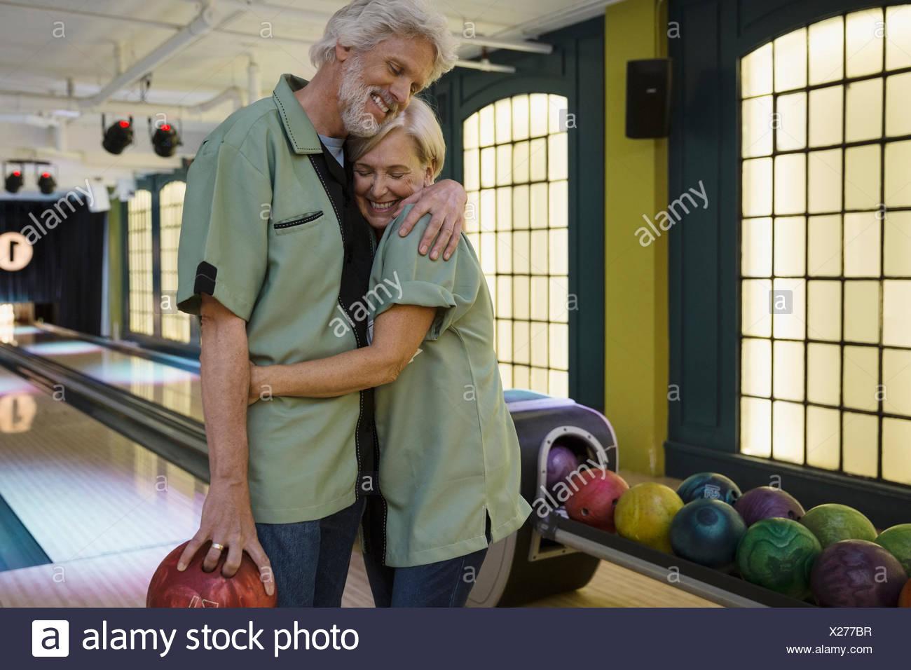 Pareja en camisas de bolera abrazando a bolera Imagen De Stock