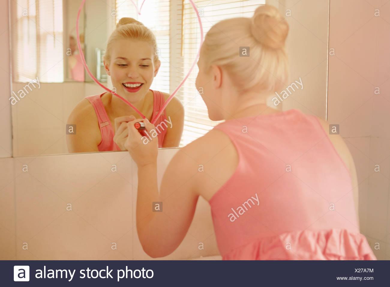 Mujer joven en el cuarto de baño en forma de corazón de dibujo con lápiz labial en el espejo Imagen De Stock