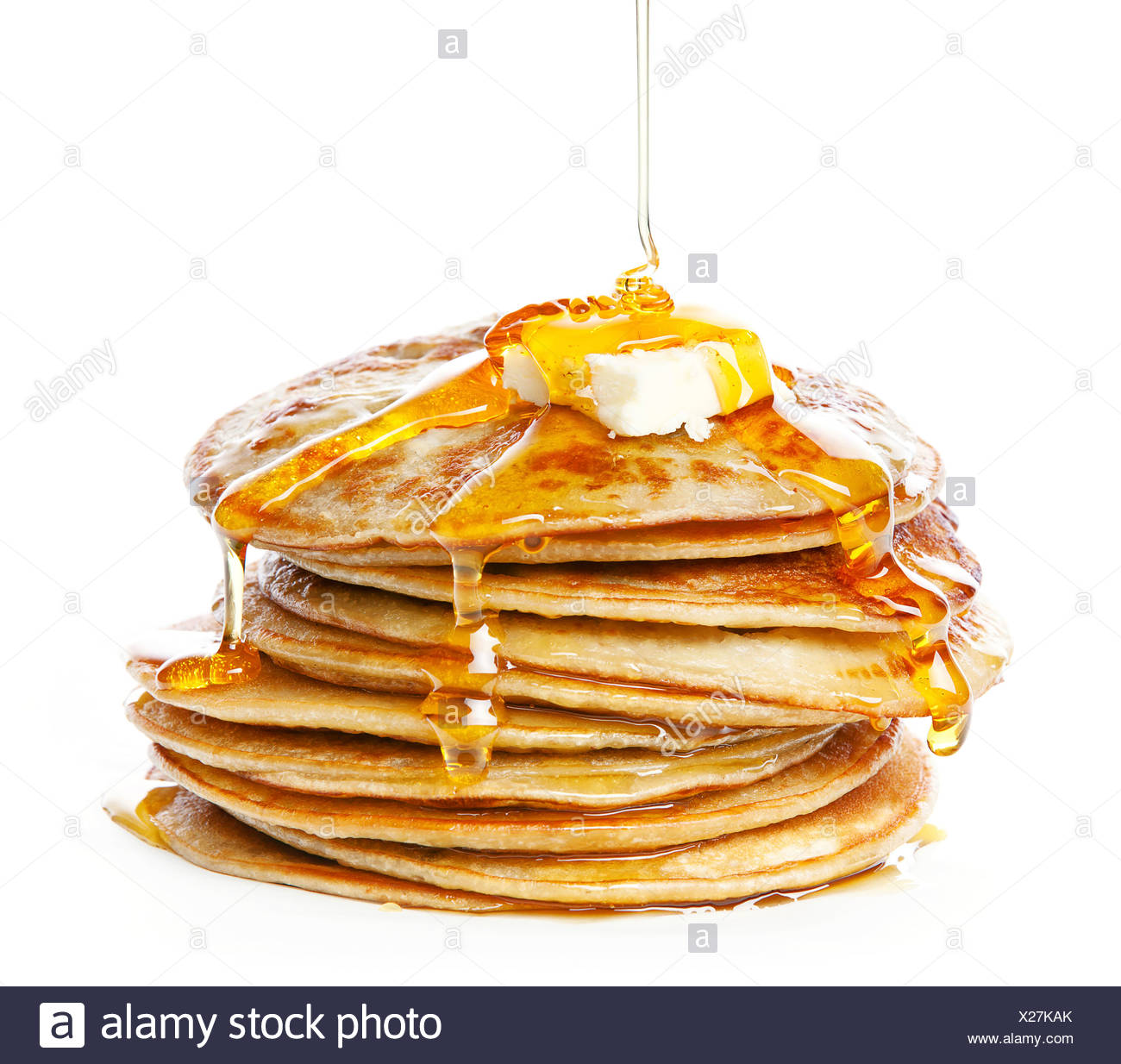 Pila de pequeñas tortitas en almíbar sobre fondo blanco. Imagen De Stock