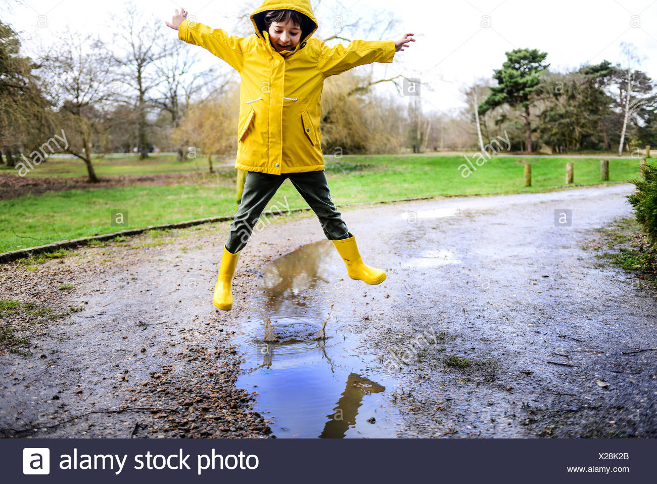 Chico en anorak amarillo saltar por encima de charco en park Imagen De Stock
