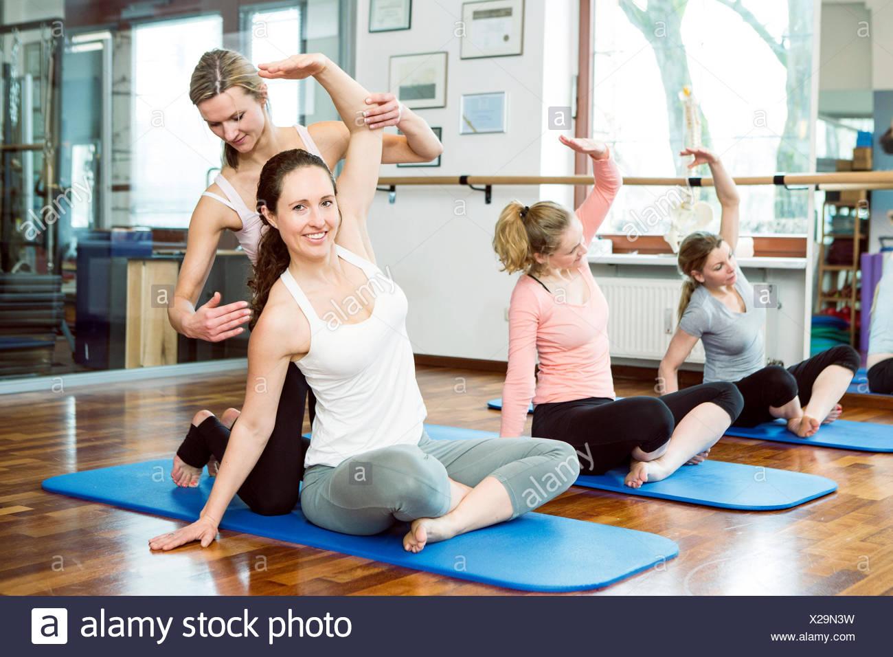 Instructor apoya a las mujeres estiramiento armas en clase de Pilates Imagen De Stock