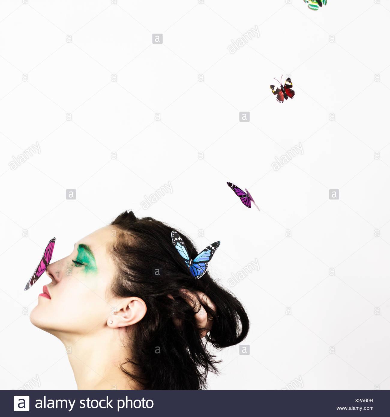 Mujer con mariposas en la nariz Imagen De Stock