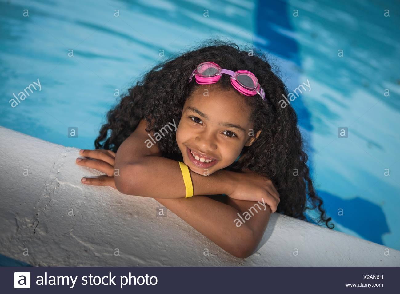 Retrato de chica con rizado pelo negro colgando sobre el borde de la piscina, mirando a la cámara sonriendo Imagen De Stock