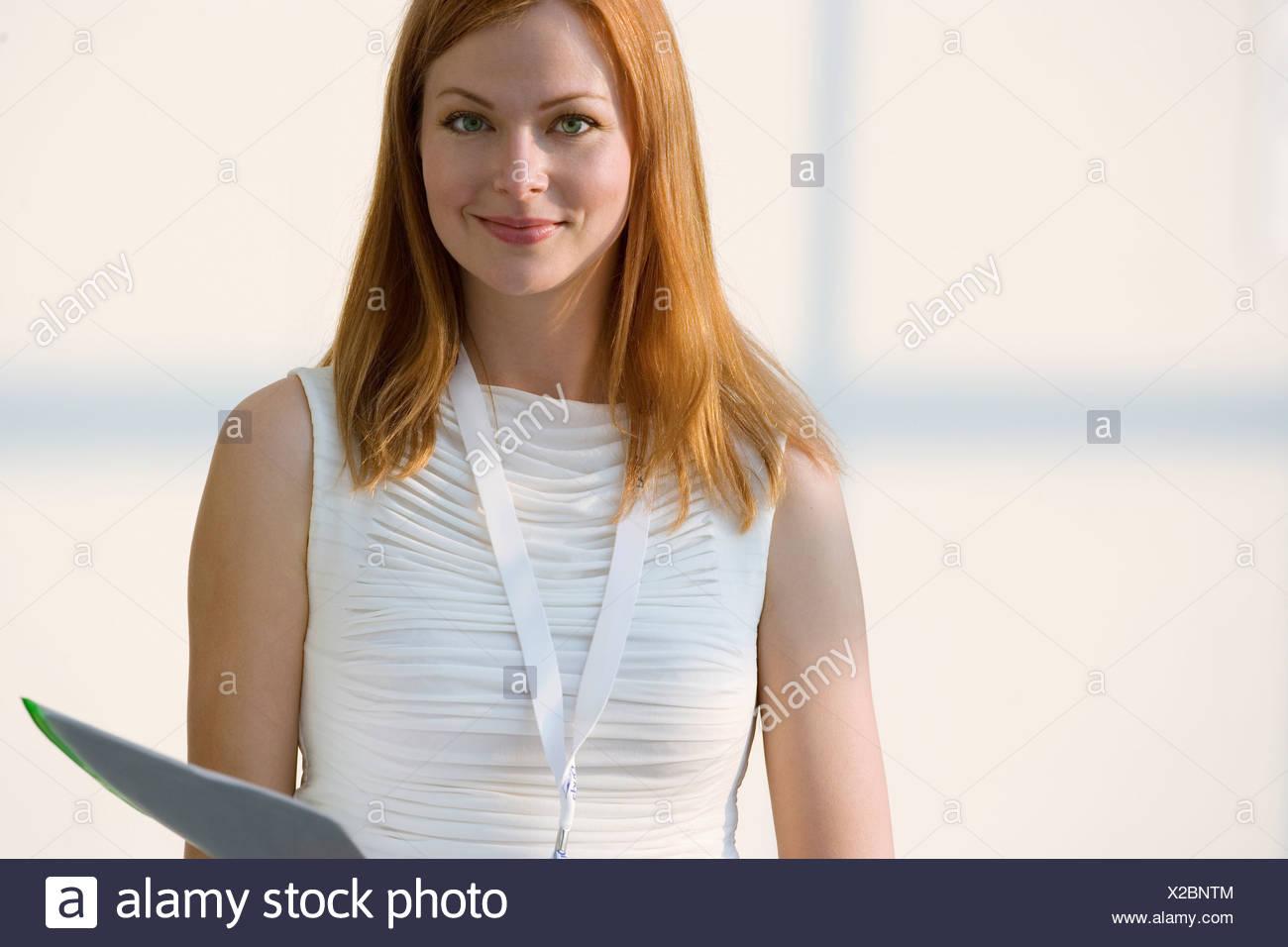 Mujer de blanco sin mangas celebración carpeta sonriente retrato vista frontal Imagen De Stock