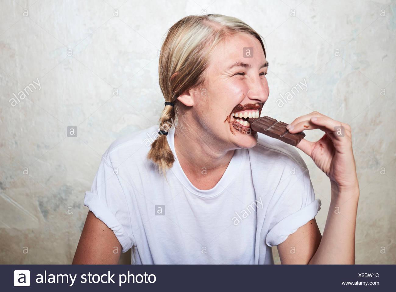 Mujer comiendo barra de chocolate, chocolate alrededor de la boca, riendo Imagen De Stock