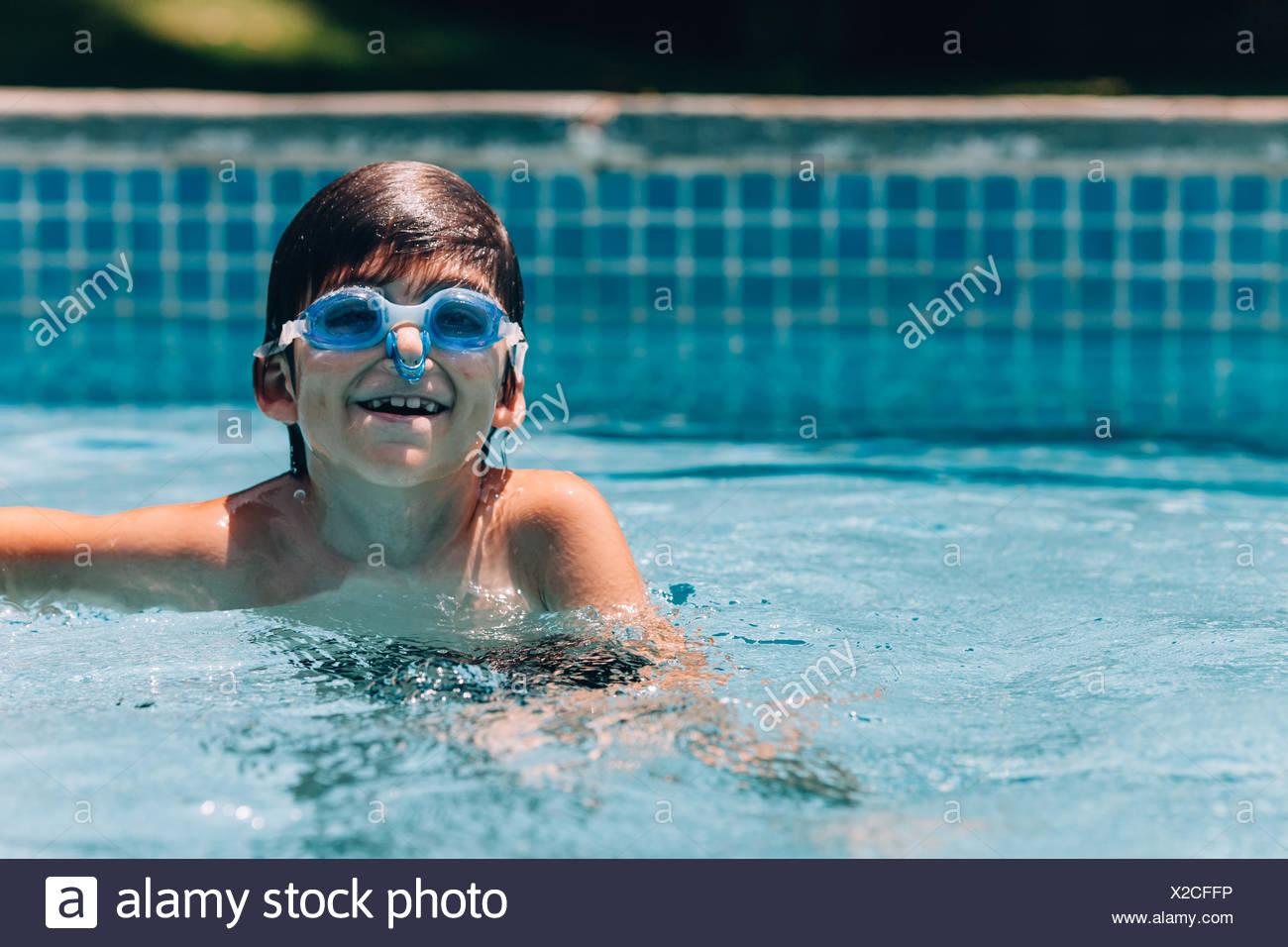 Chico sonriente gafas protectoras y pinza para nariz en piscina Imagen De Stock