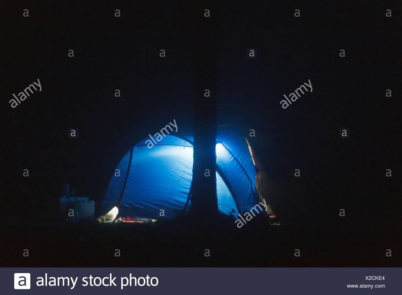 La cúpula iluminada azul carpa en el campo de noche Imagen De Stock