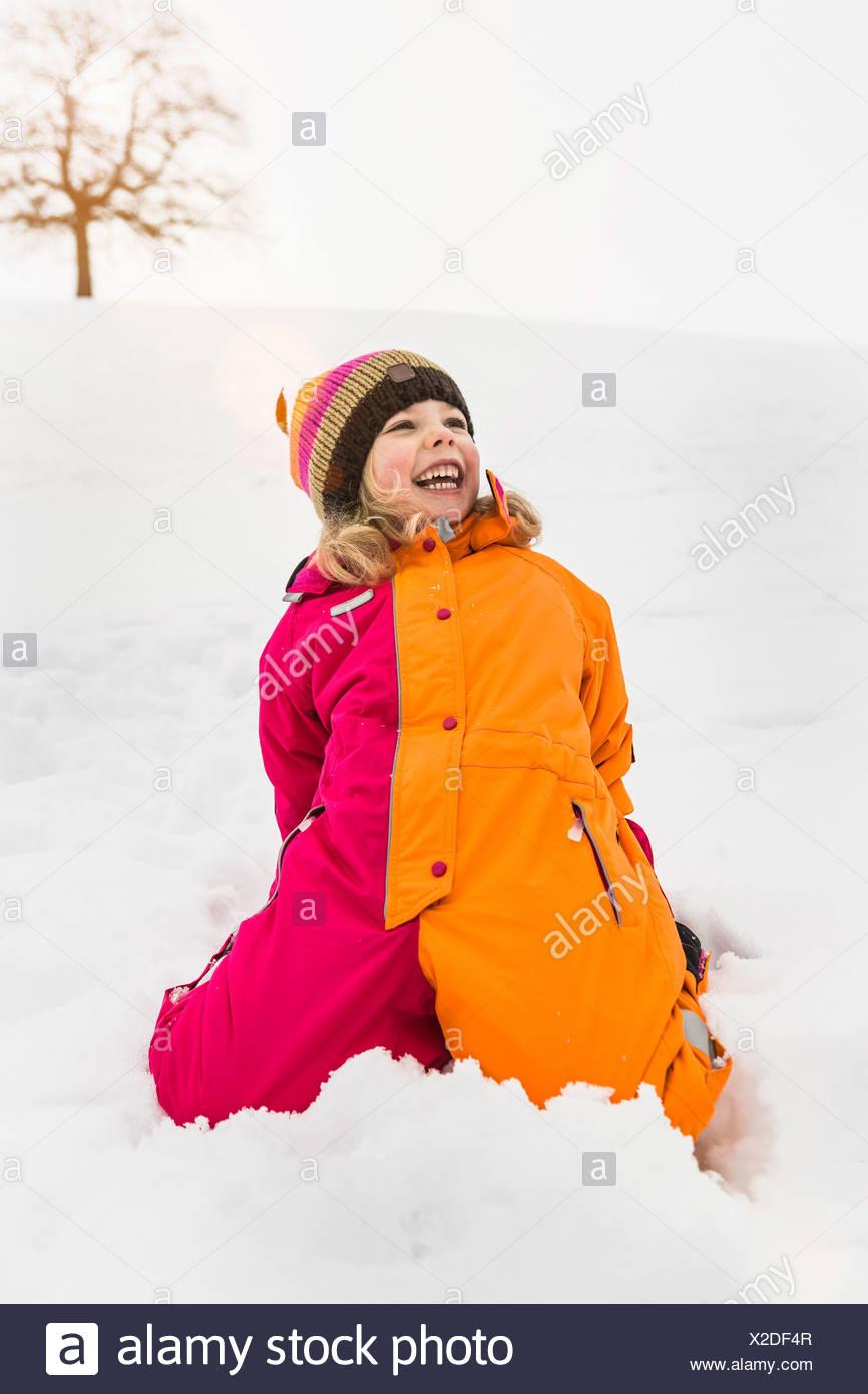 Retrato de chica que llevaba snowsuit arrodillado sobre la nieve Imagen De Stock