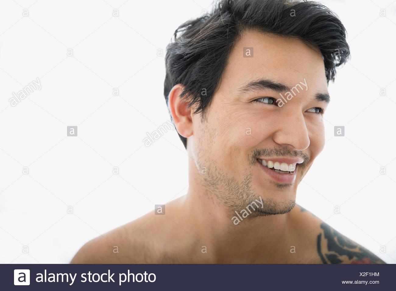 Hombre sonriendo con cabello negro en busca de distancia Foto de stock