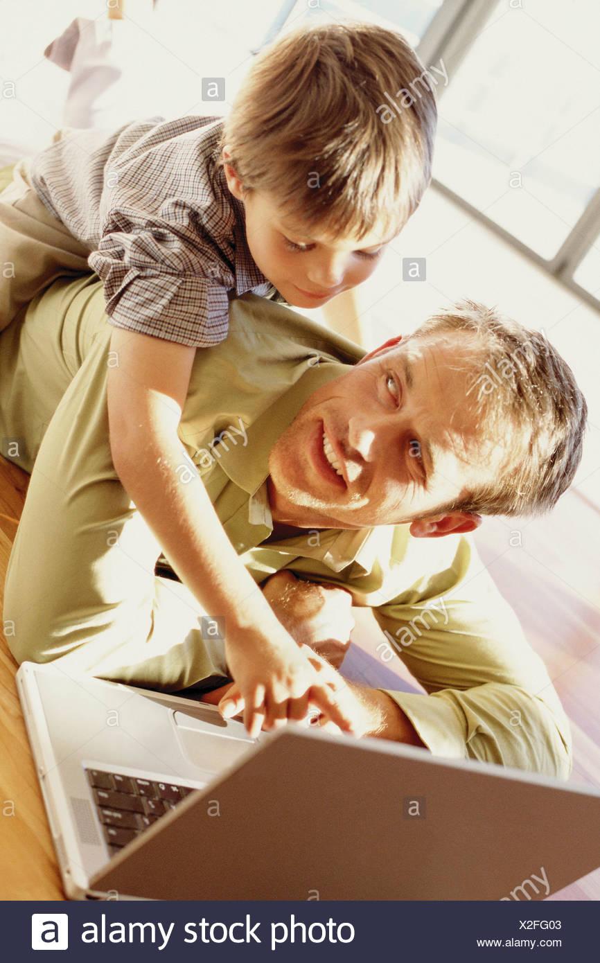 Padre e hijo jugando con un portátil Foto de stock