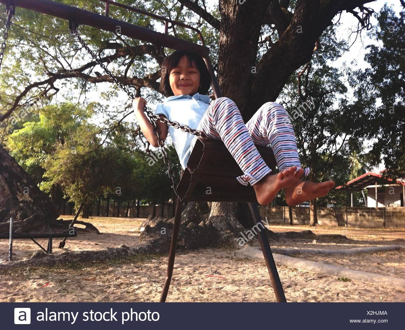 Chica balanceándose en la cadena Swing Ride y sonriente Imagen De Stock