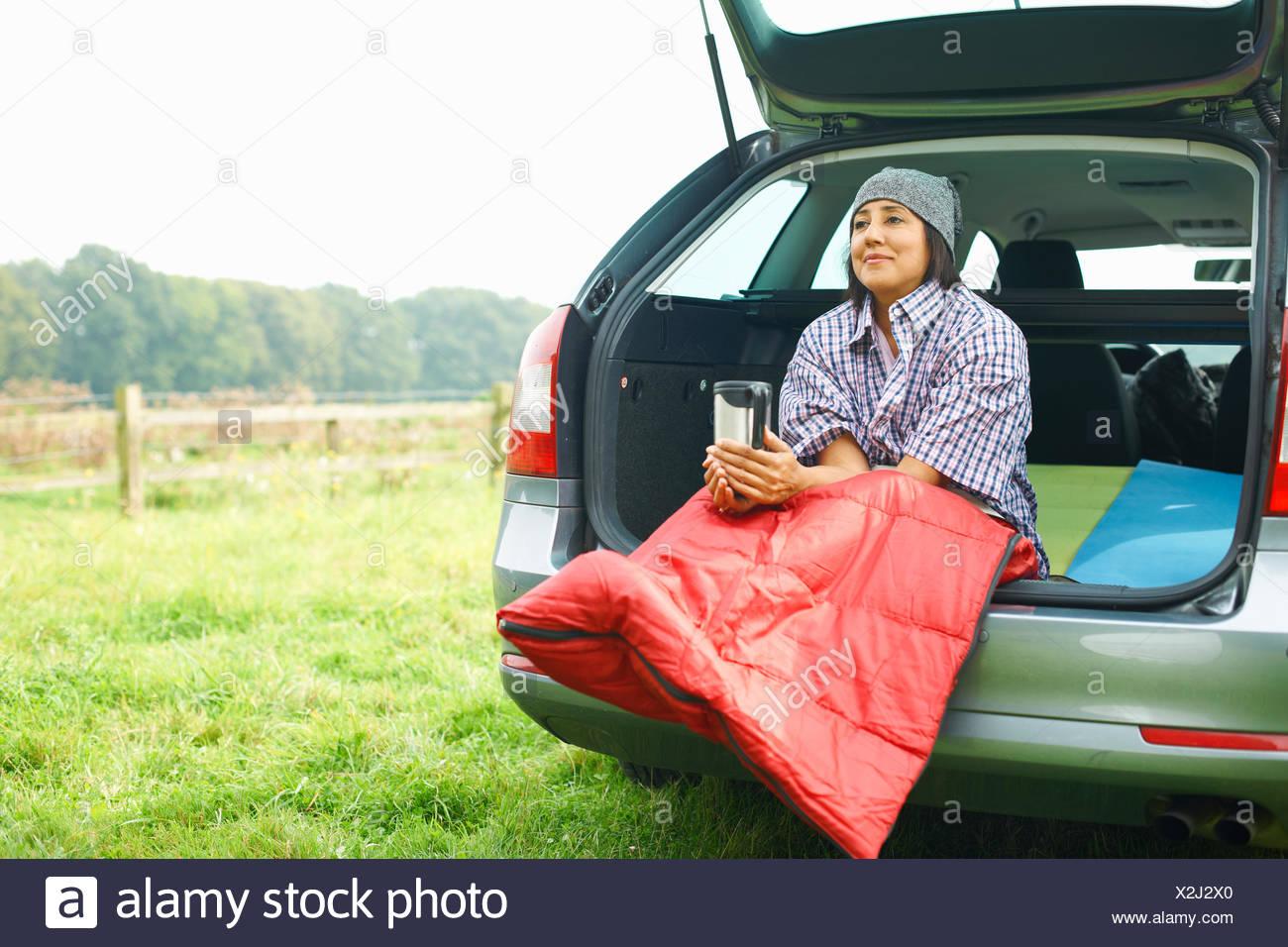Mujer sentada en la parte trasera del coche con las piernas metidas en bolsa de dormir. Imagen De Stock