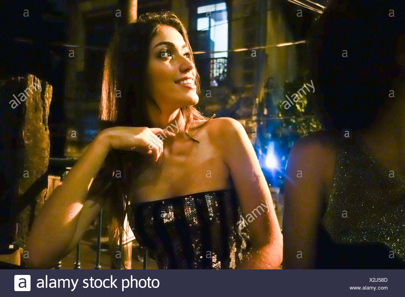 Dos mujeres jóvenes sentados en el bar, mirando lejos Imagen De Stock