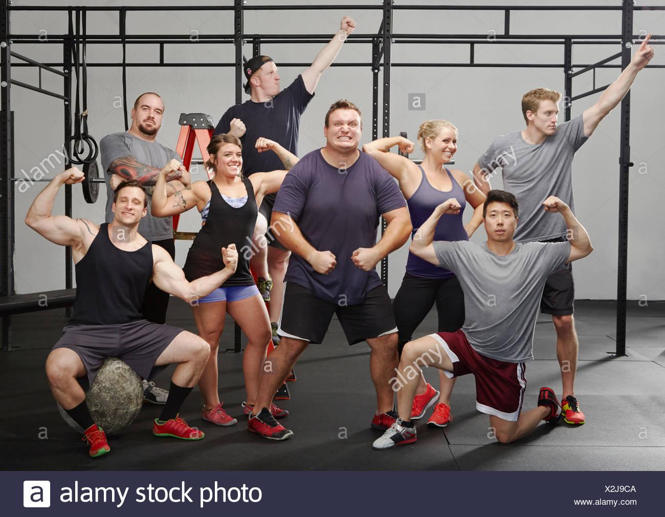 Retrato de ocho personas flexionando los músculos en el gimnasio Imagen De Stock
