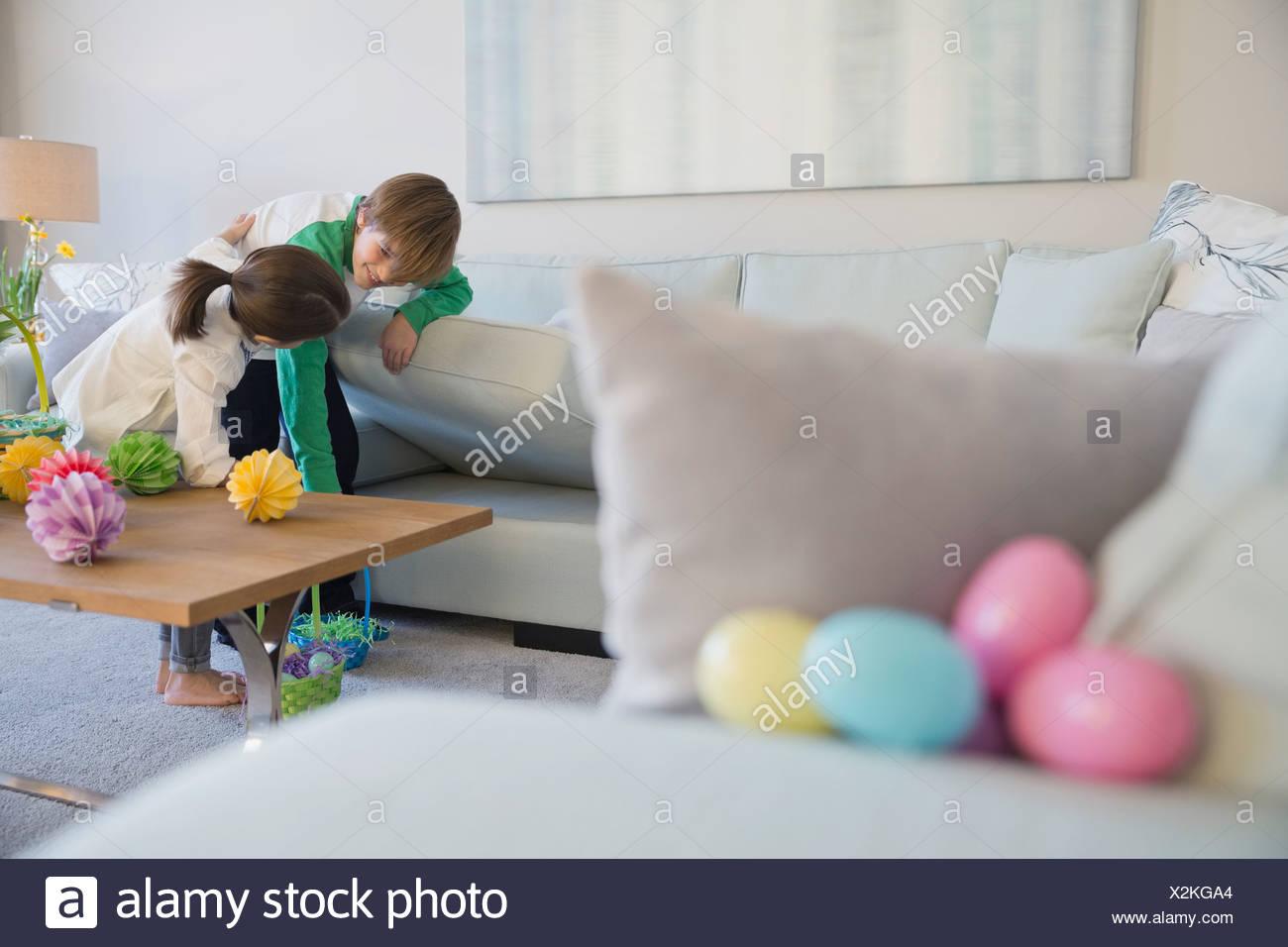 Hermanos buscar huevos de Pascua en el salón Imagen De Stock