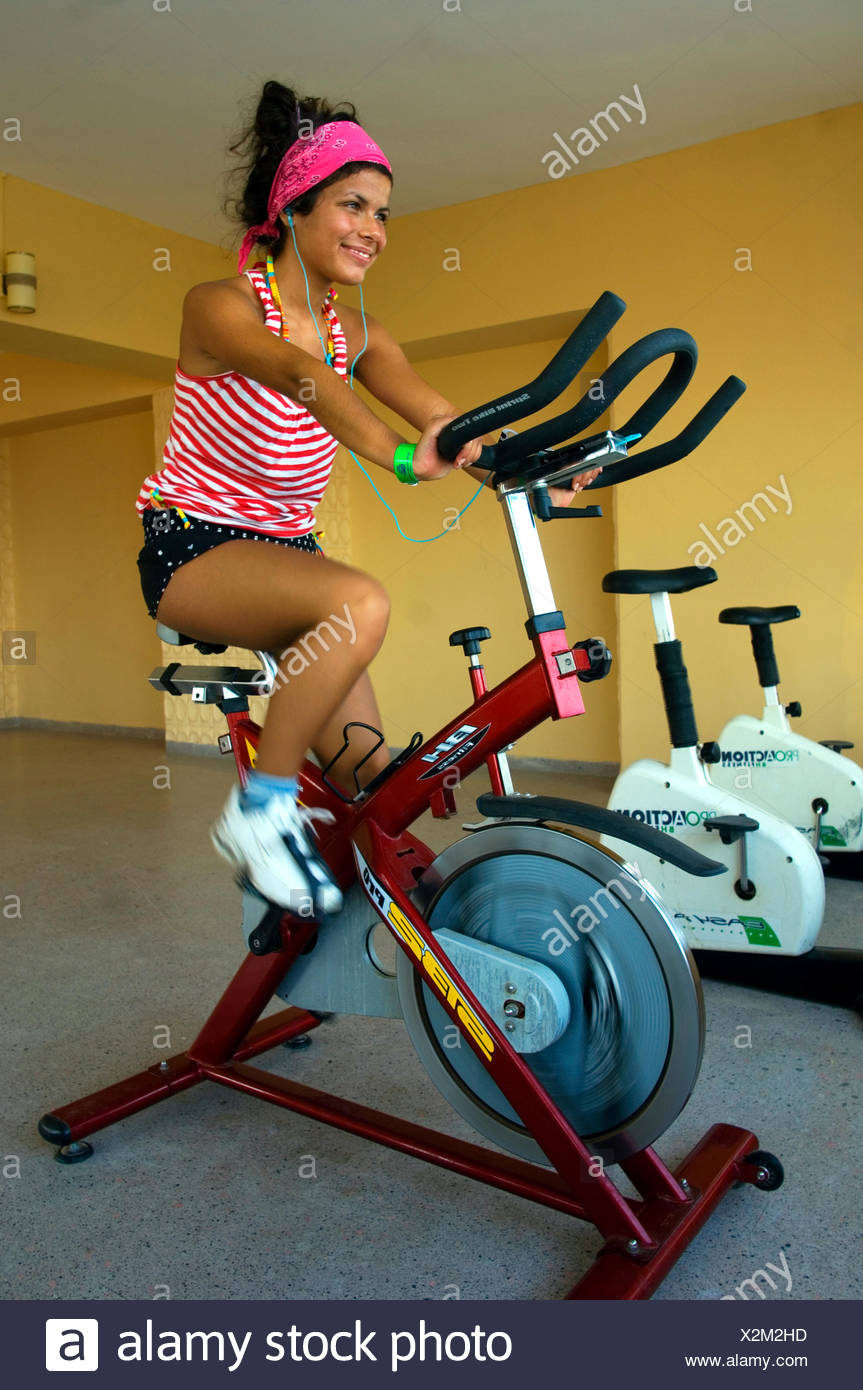 Mujer joven sentada sobre una máquina de ejercicio en el gimnasio Imagen De Stock