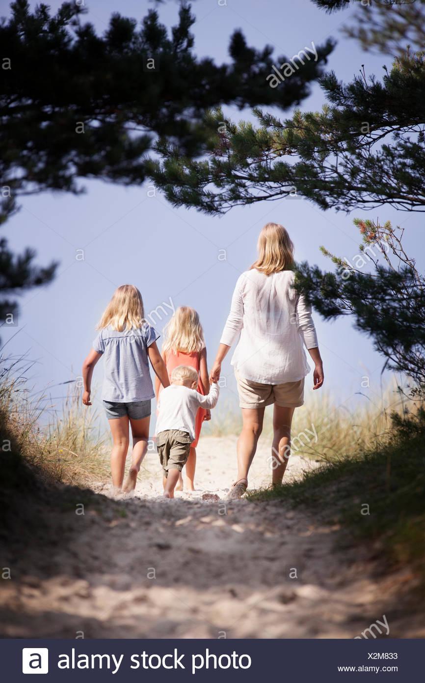 Suecia, Gotland, Faro, Skar, madre con su hijo (2-3) y las hijas (8-9, 10-11) caminando por la senda Imagen De Stock