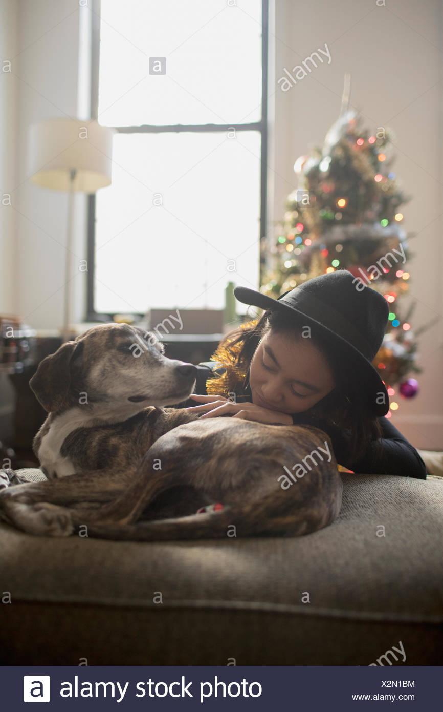 Una mujer joven con un perro en un sofá Imagen De Stock