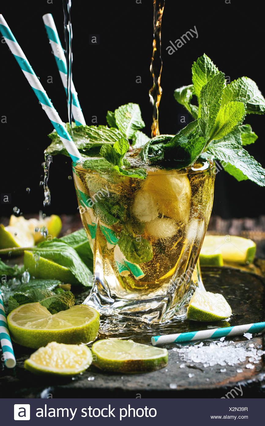Copa de cóctel mojito con verter el ron y la soda, menta fresca, limón y cubitos de hielo sobre fondo negro. Foto de stock