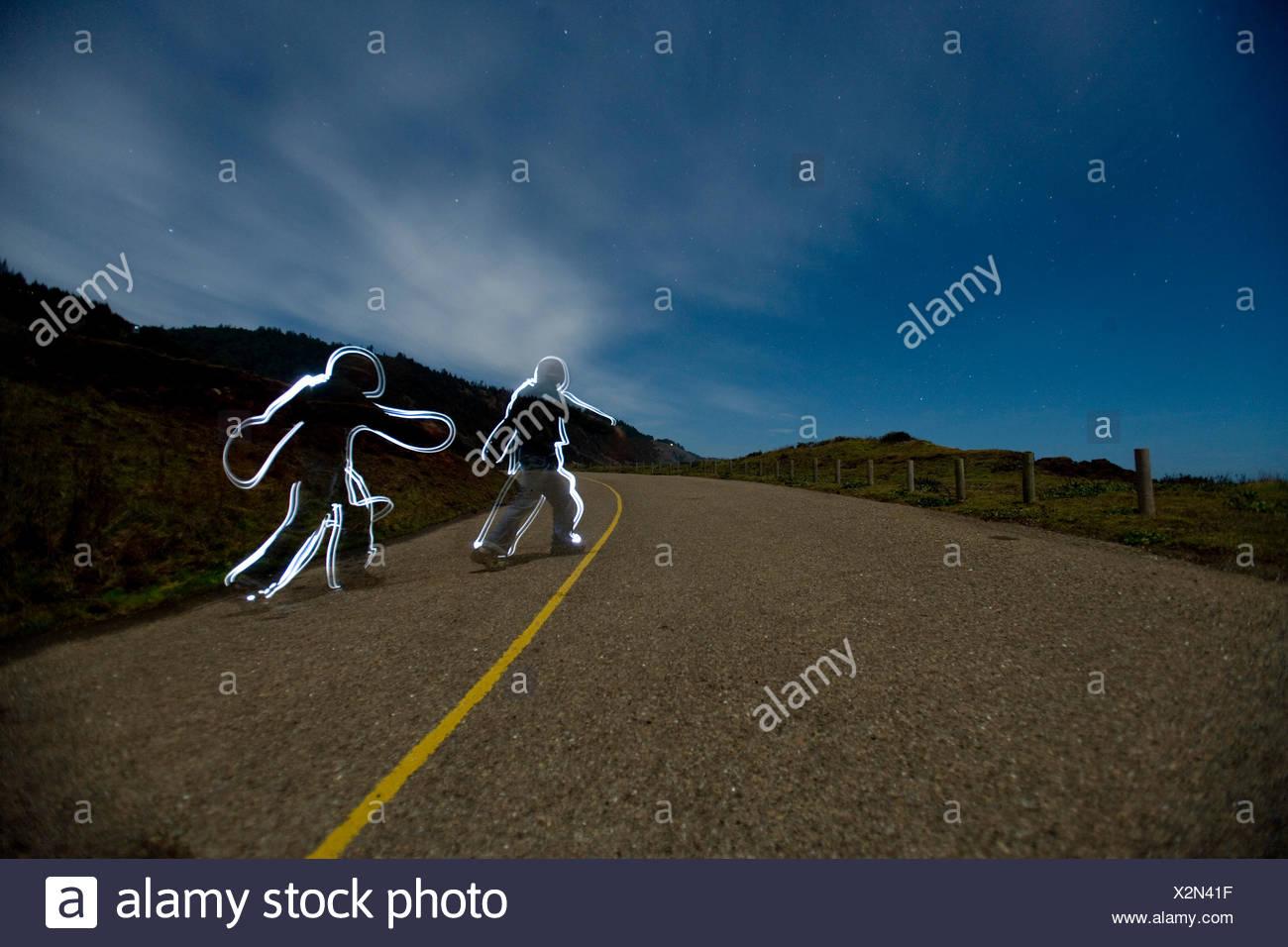 Lightpainting imagen de dos seres humanos caminando por una carretera Imagen De Stock