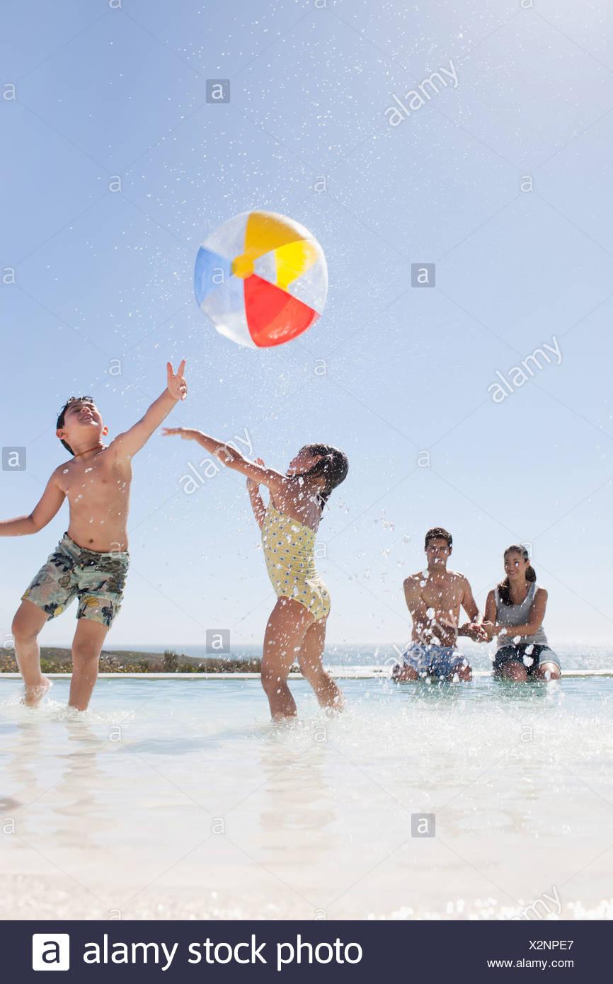 Familia jugando con la bola en la piscina Imagen De Stock