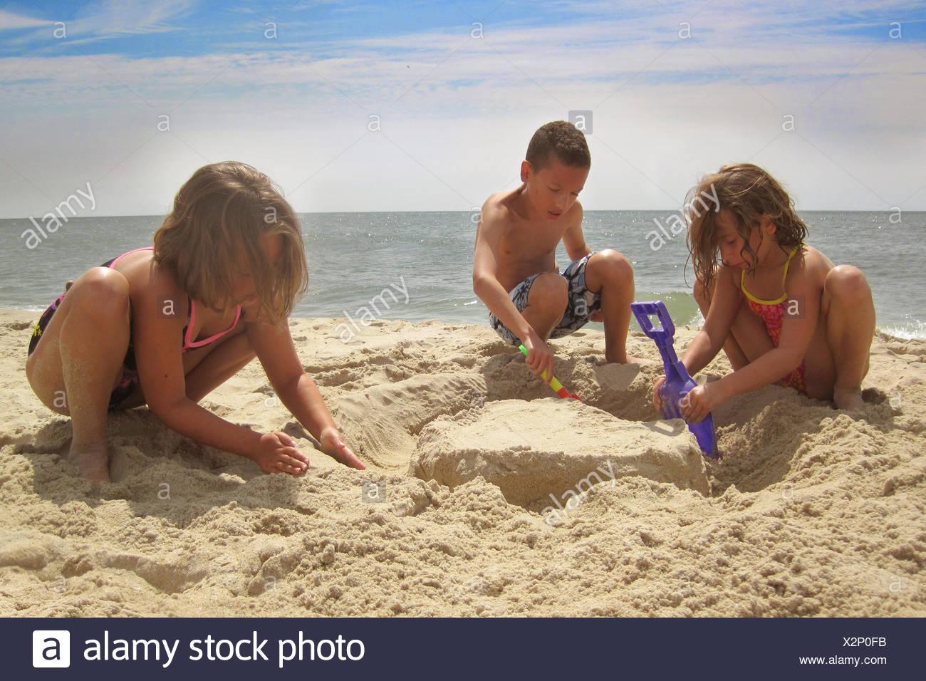 Tres hermanos (6-7, 8-9, 10-11) en la playa Imagen De Stock