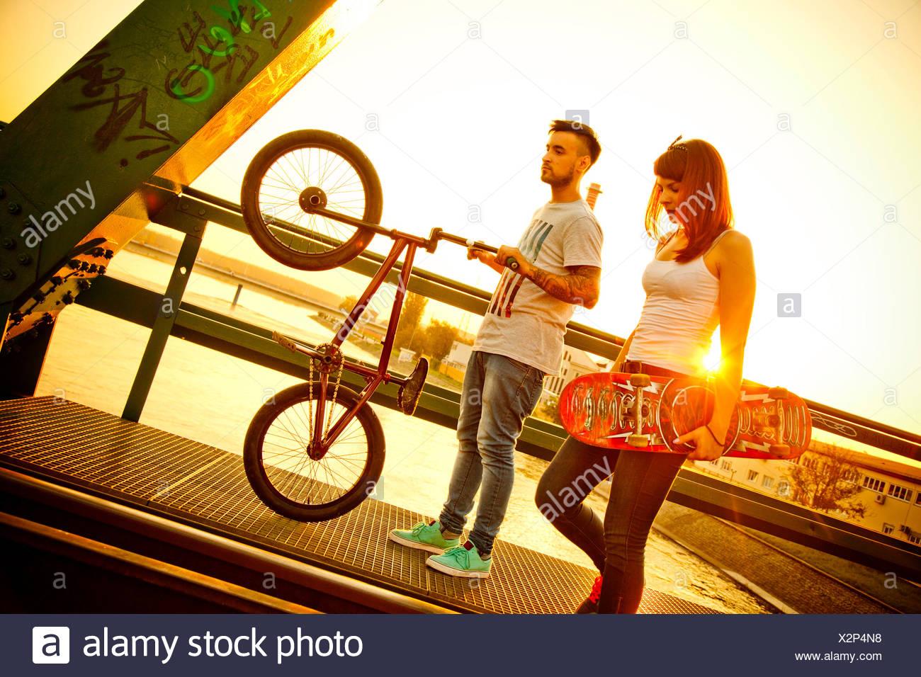 Pareja joven con skate y bicicletas BMX afuera Foto de stock