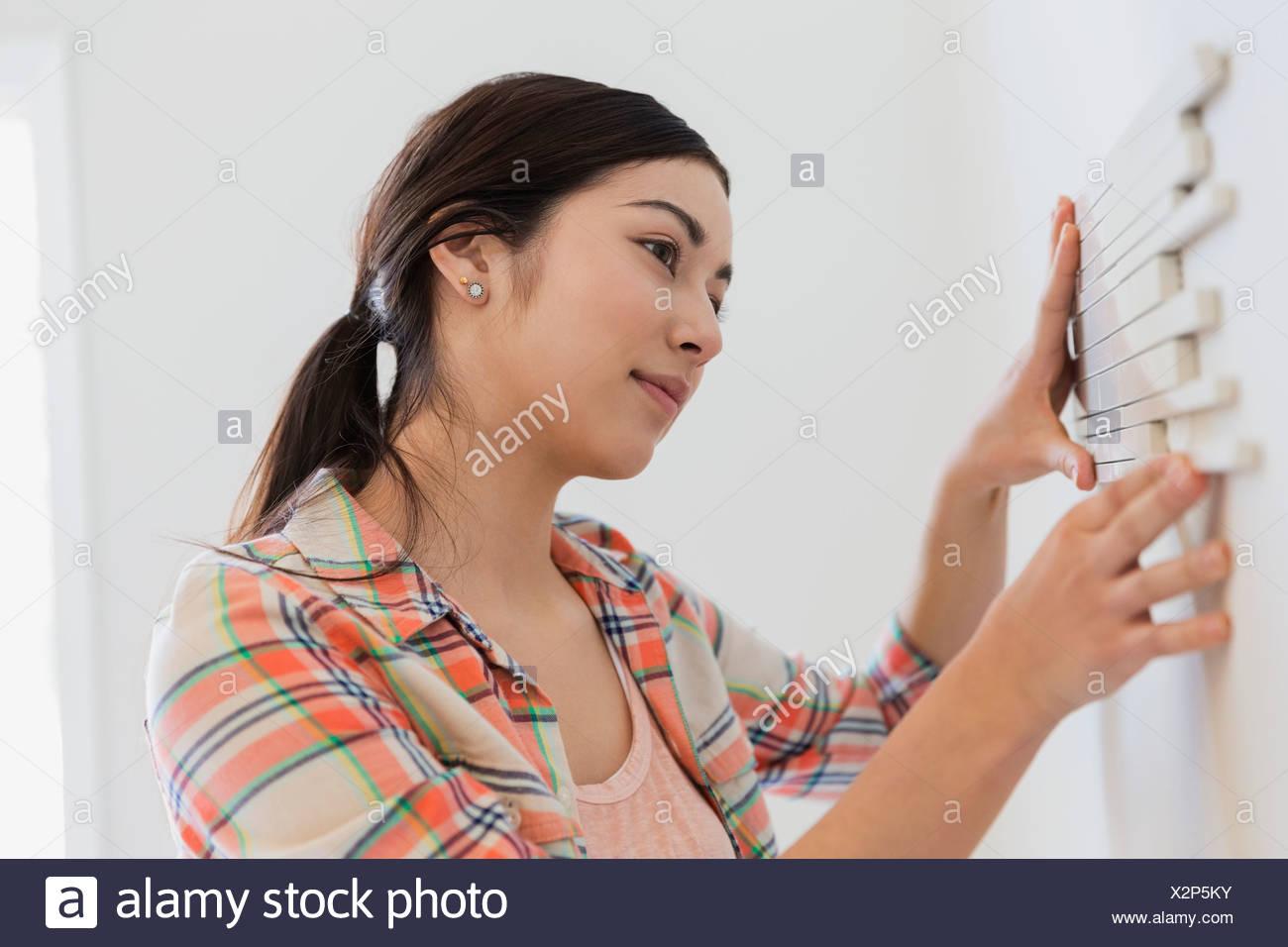 Mujer joven decorando paredes con azulejos en casa Imagen De Stock