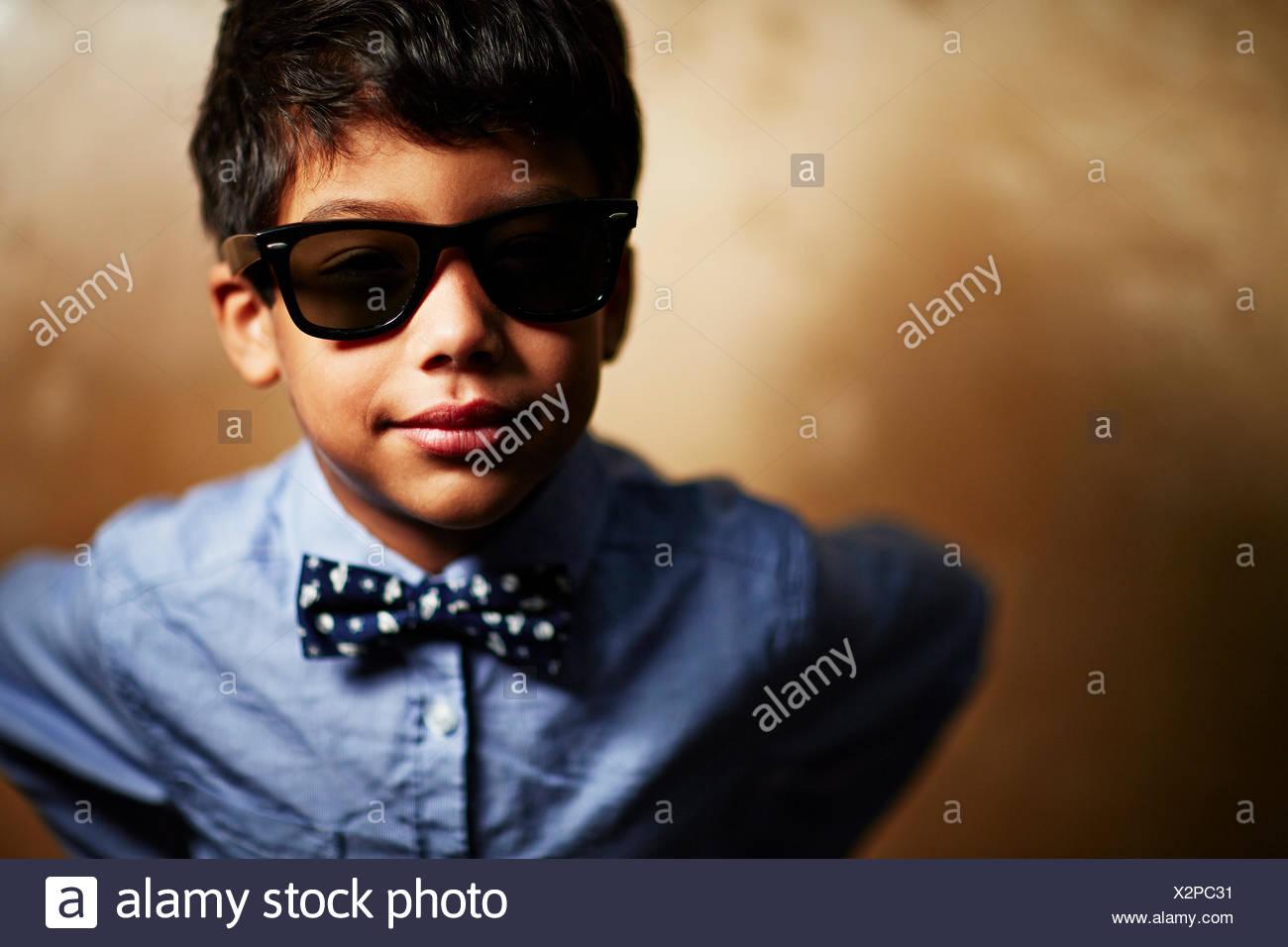 Niño con gafas de sol y pajarita Foto de stock