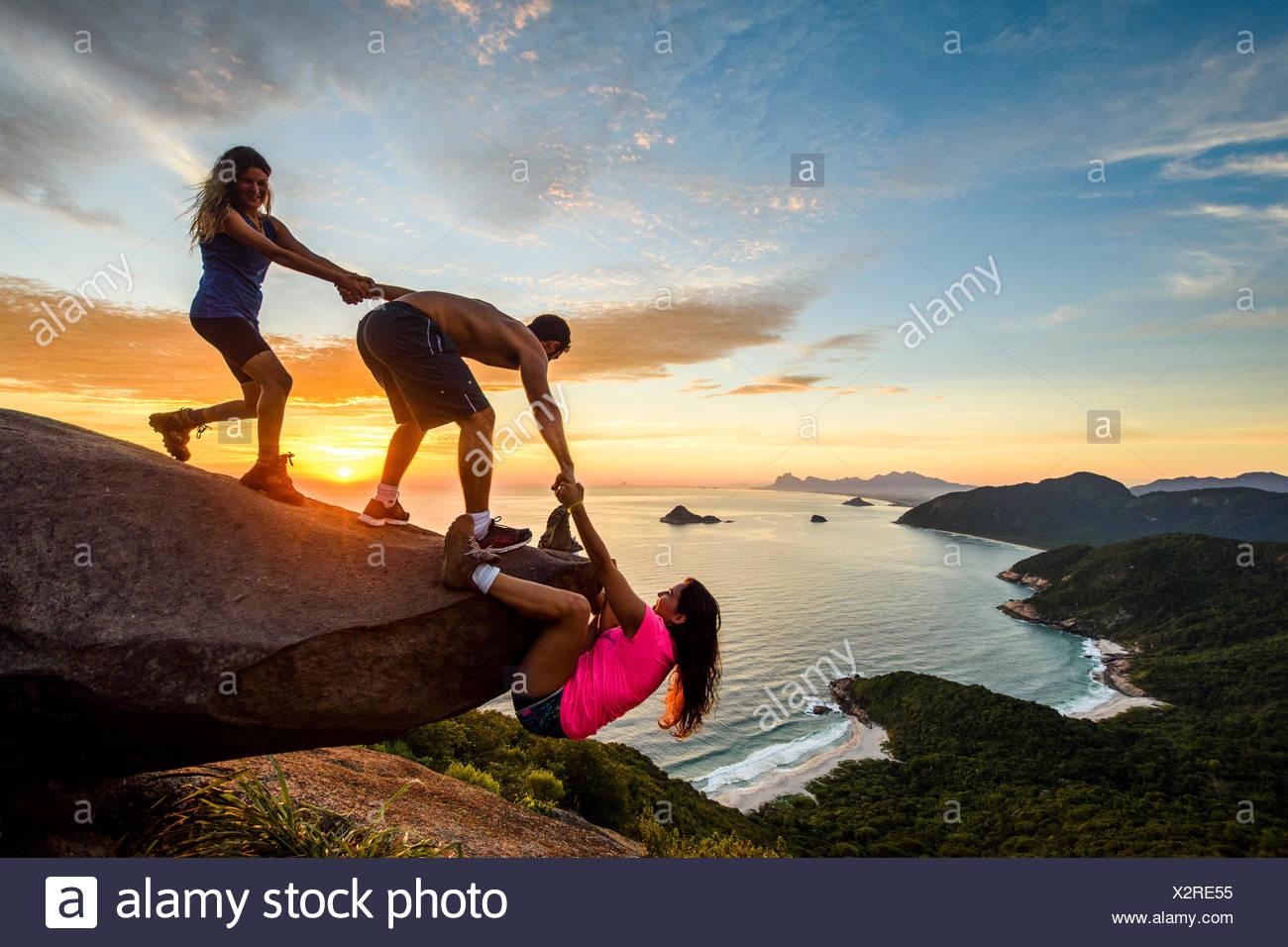 Dos personas que ayudaban a la mujer rock subir al atardecer, Pedra do telégrafo, Río de Janeiro, Brasil Imagen De Stock