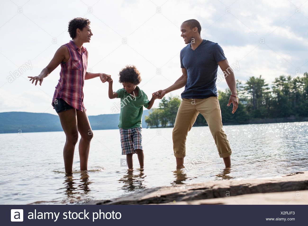 Una familia, los padres y el hijo de un lago en verano. Imagen De Stock
