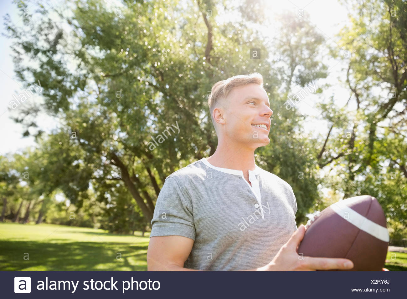 Hombre sonriente jugando al fútbol en el parque soleado de verano Imagen De  Stock a25aae5bb9ba9