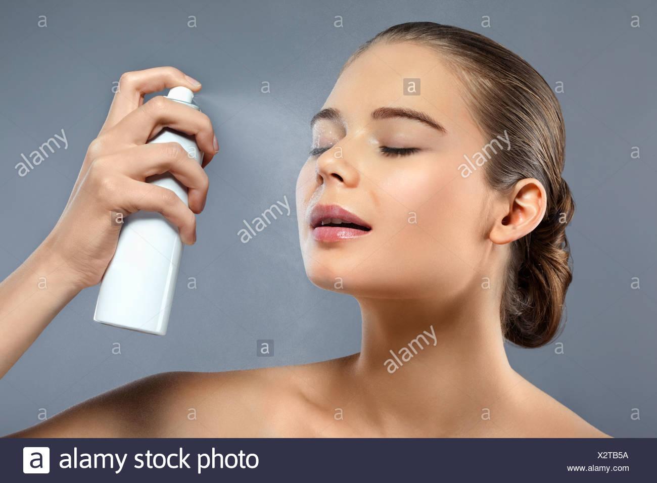 Una mujer rociando su rostro con spray hidratante Imagen De Stock