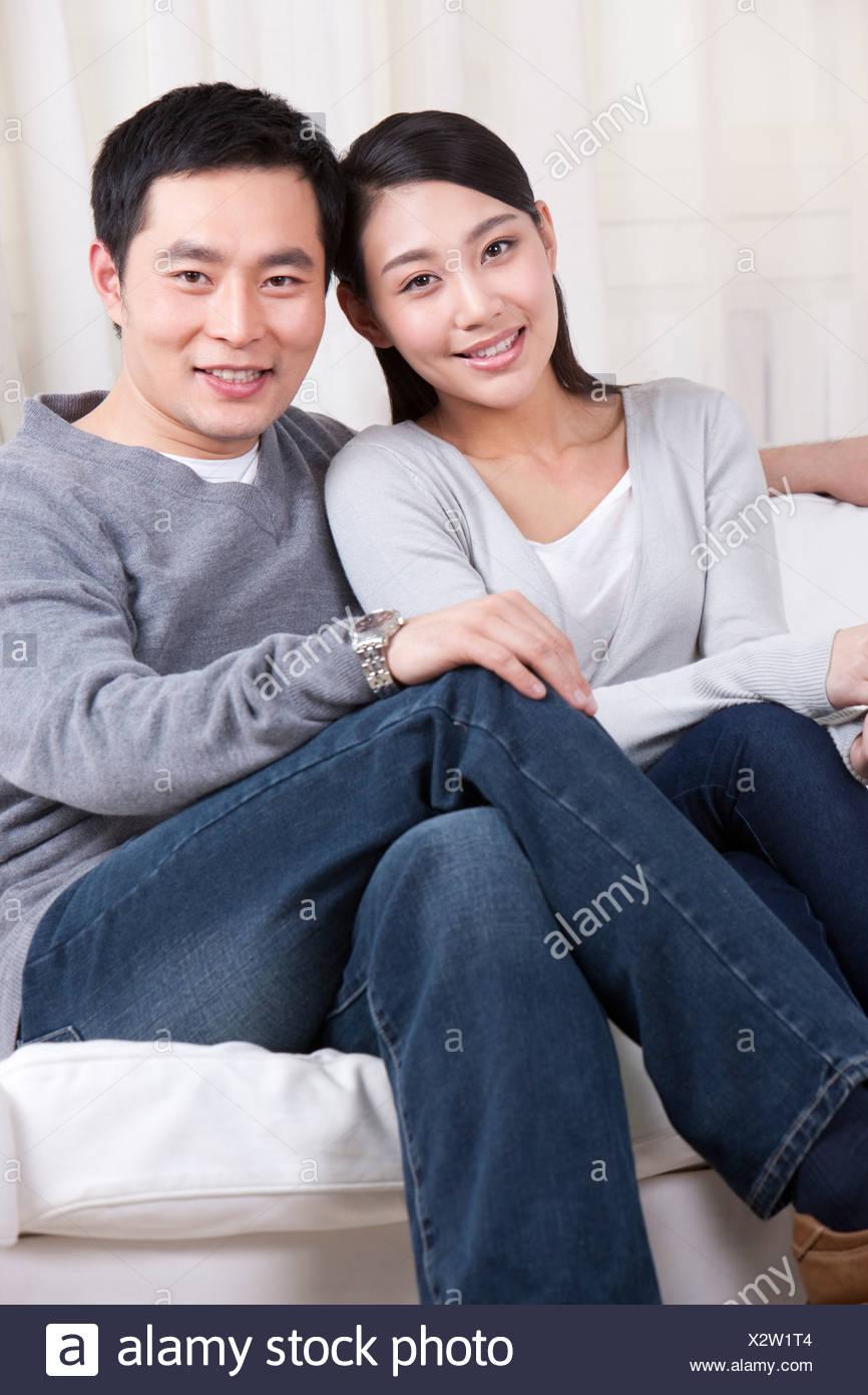 Pareja joven sentado en el sofá Imagen De Stock